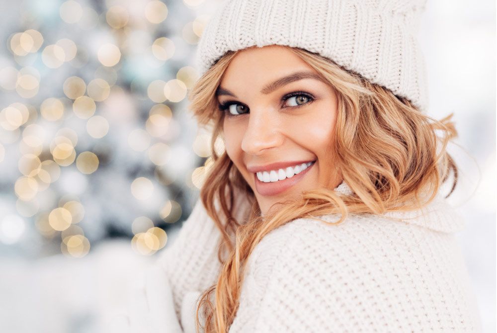 Blonde woman in a white beanie smiles with a winter-white smile against a sparkling New Year's tree
